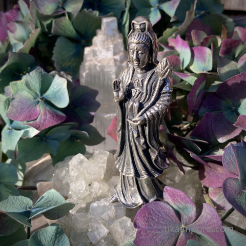 Quan Yin large brass statuette on an altar with crystals and hydrangea blossoms