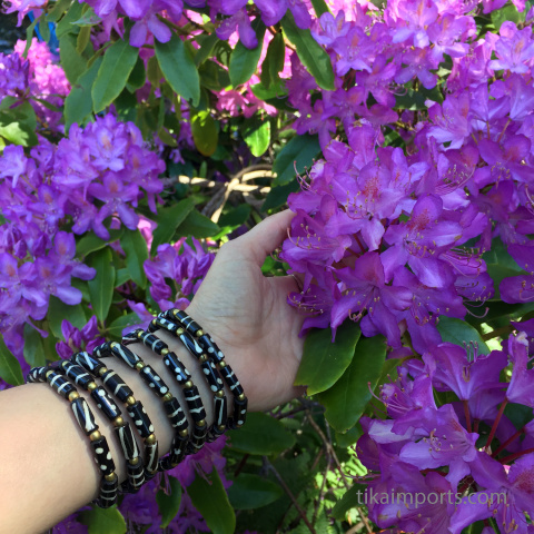 batik bone bracelets being worn in front of purple rhododendron