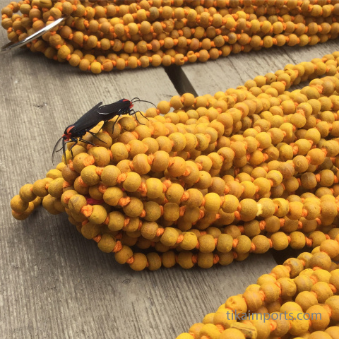two love bugs resting on a hank of knotted haldi turmeric mala
