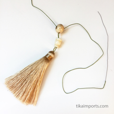 tassel and guru bead shown being strung together