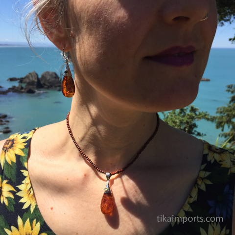 amber honey drop earrings and pendant set with a view of the Pacific ocean