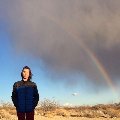 Julie in the desert with a stormy rainbow behind her