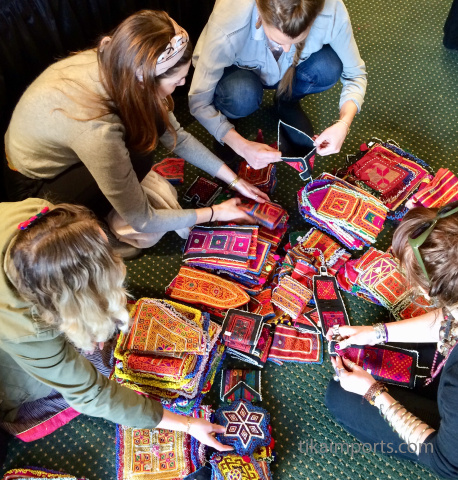 Tika girls looking through a new shipment of vintage afghani purses and wallets
