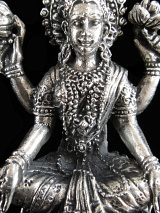 closeup of seated Lakshmi brass deity statue, the Goddess of abundance and prosperity