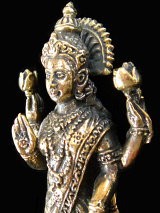 closeup of standing Lakshmi brass deity statue, the Goddess of abundance and prosperity