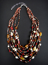 Glass and natural stone multi-strand necklace in tones of red and brown.