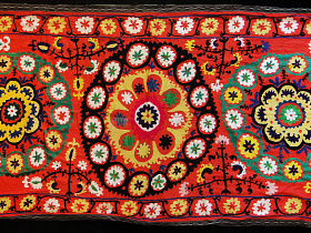 Long, fancy embroidered textile on coral cotton fabric