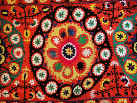 center detail of long, fancy embroidered textile on coral cotton fabric