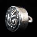 side view of sterling silver repouse shank-button with fleur de lis design