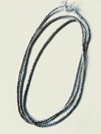 coiled strand of tiny African silver-colored brass thread beads.