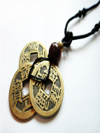 Black adjustable cord necklace with pendant made from three brass Chinese coin replicas, horn, and brass accent beads.
