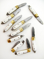 showing an assortment of ten white Mini knives that open and close