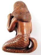 handcarved boxwood netsuke of mermaid combing her hair handcarved boxwood netsuke of mermaid brushing her hair