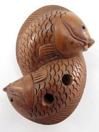 netsuke of two intertwining fish showing hole through reverse side of fish