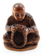 handcarved boxwood netsuke of seated Buddha holding prayer mala beads