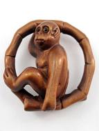 handcarved boxwood netsuke of monkey sitting in a bamboo hoop