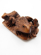 handcarved boxwood netsuke of three frogs on a leaf