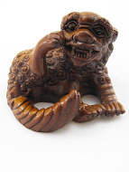 handcarved boxwood netsuke of scratching foo dog