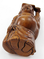 handcarved boxwood netsuke of buddha with fan showing view of underside