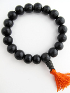 Ebony wood beads strung into a stretch bracelet with elastic cord and tassel