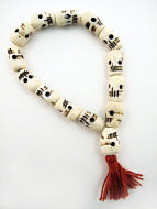 Handcarved bone skull beads strung into a stretch bracelet with elastic cord and tassel