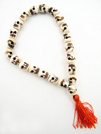 Small handcarved bone skull beads strung into a stretch bracelet with elastic cord and tassel