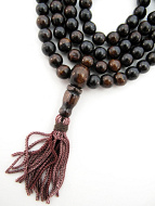 detail of bone mala prayer beads showing tassels and counter beads