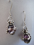Sterling silver earrings featuring flourite orbs in silver enclosures topped with garnet accent stones