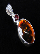 Sterling silver pendant with decorative bail featuring amber topped with garnet accent stone