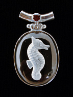 Sterling silver pendant featuring quartz crystal carved with the image of a sea horse and a garnet accent stone on bail