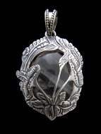 Sterling silver pendant featuring rose quartz held in an intricate floral setting