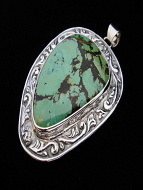 Sterling silver pendant featuring natural turquoise framed by a hand-repousséed setting