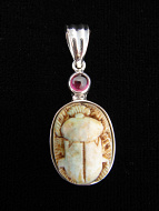 Sterling silver pendant featuring a carved faience scarab with garnet accent stone