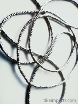 closeup view of tiny African silver-colored brass thread beads.