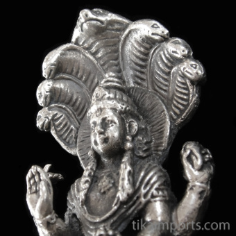 closeup of Vishnu brass deity statue, the Supreme Being, protector of the universe seated on the coiled serpent Shesha