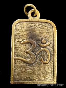 back of Durga brass deity pendant showing 'om' symbol