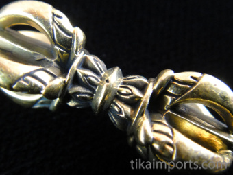 closeup of small dorje brass pendant, a ritual object representing firmness of spirit
