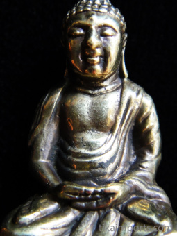 closeup of Buddha brass deity pendant, the sage on whose teachings Buddhism was founded