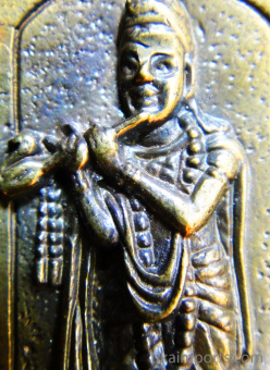 closeup of Krishna brass deity pendant, god of love and compassion playing his flute