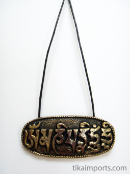 Om Mani Padme Hum brass pendant, shown on a cord
