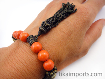 Fancy tassle bracelet in 'persimmon' color palatte featuring brass, carved bone and glass beads.