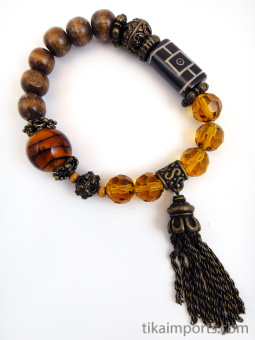 Fancy tassle bracelet in 'honey' color palatte featuring brass, carved bone, wood and glass beads.