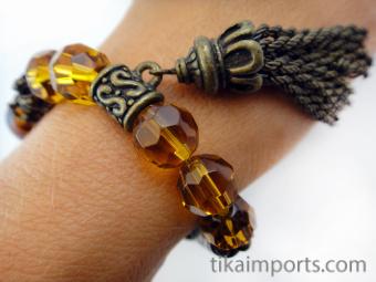 "Fancy ""Honey"" tassel bracelet, featuring brass, carved bone and glass beads."