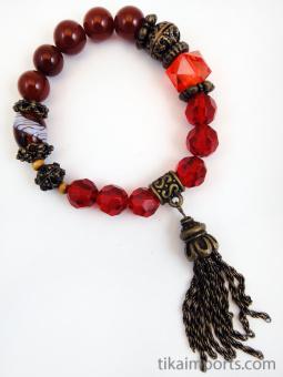 Fancy tassle bracelet in 'pomegranate' color palatte featuring carnelian, brass, wood, glass, and one plastic bead
