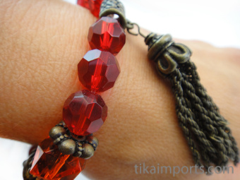 closeup view of Fancy tassle bracelet in 'pomegranate' color palatte featuring carnelian, brass, wood, glass, and one plastic bead