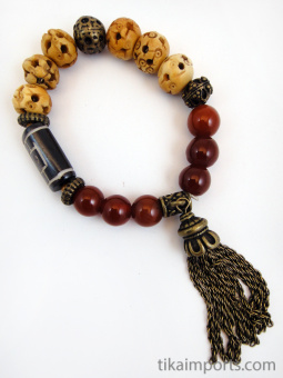 Fancy tassle bracelet in 'currant' color palatte featuring brass, carved bone and carnelian beads.