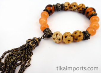 Fancy tassle bracelet in 'peach' color palette featuring dyed stone, carved bone, brass, and glass beads.