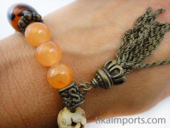 "Fancy ""Peach"" tassel bracelet, featuring brass, carved bone and glass beads."