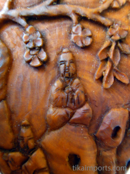 handcarved boxwood bottle ornament featuring image of Buddha on a mountain