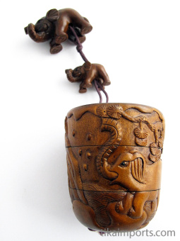 handcarved barrel-shaped boxwood Inro box with carved elephants and three inner compartments.